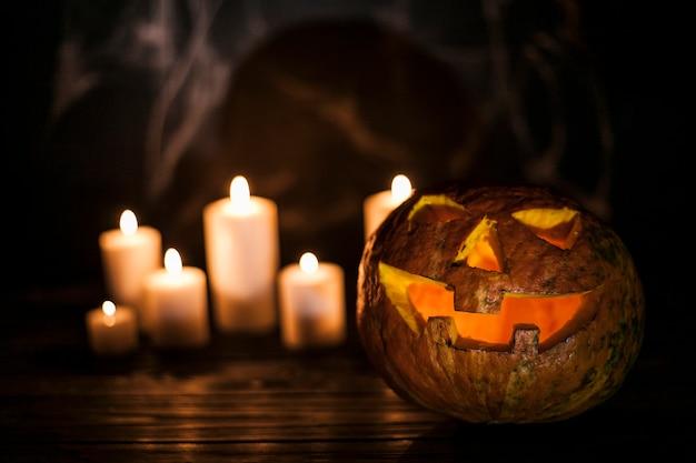 Creepy calabaza tallada y velas blancas Foto gratis