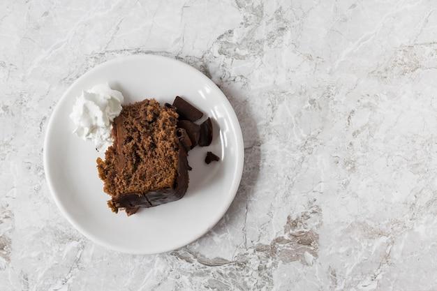 Crema batida y rebanada de pastel en un plato sobre el mostrador de ...