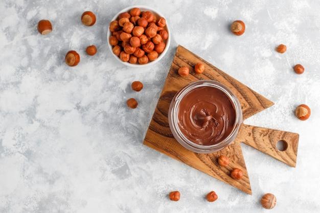 Crema de chocolate o turrón con avellanas en frasco de vidrio sobre hormigón, copyspace Foto gratis