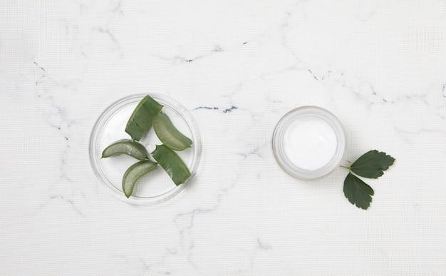 Crema corporal laica plana sobre fondo de mármol Foto gratis