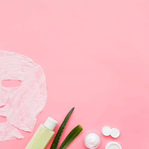 Crema para la piel de aloe vera; hoja de loción y papel mascarilla sobre fondo rosa Foto gratis