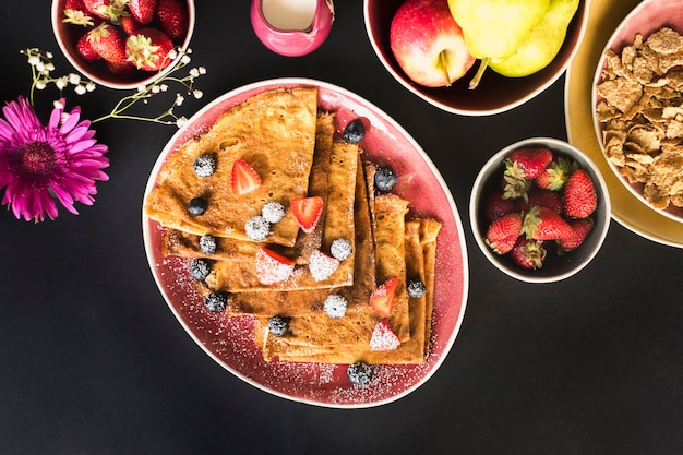 Crepe saludable con frutas sobre fondo negro Foto gratis