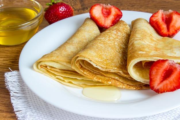 Crepes apiladas con sirope de fresa y miel. Foto Premium