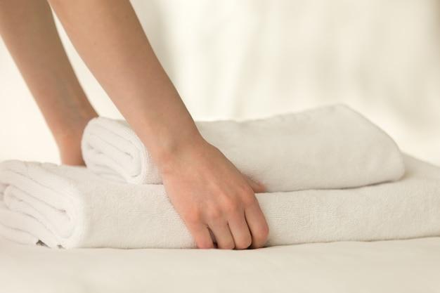 Criada colocando la pila de toallas en la cama Foto gratis