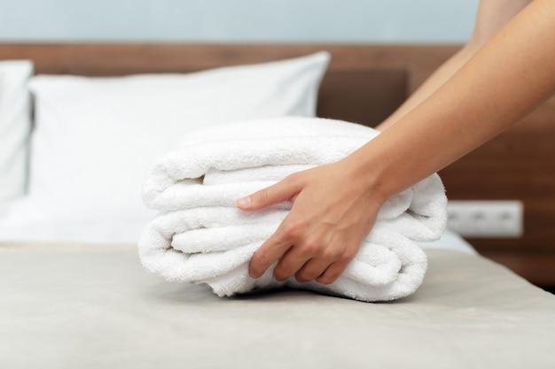 Criada con toallas limpias y frescas durante la limpieza en una habitación de hotel Foto Premium