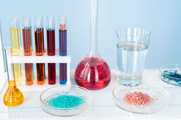 Cristalería de laboratorio químico con varios líquidos de colores en la mesa Foto Premium