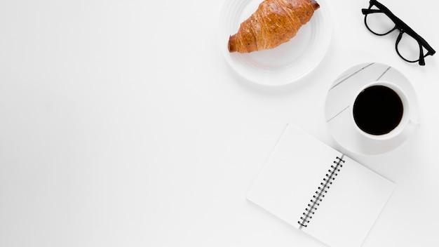 Croissant café negro y cuaderno con espacio de copia Foto gratis