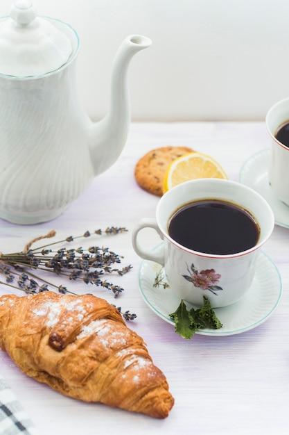 Croissant fresco con taza de té para el desayuno Foto gratis