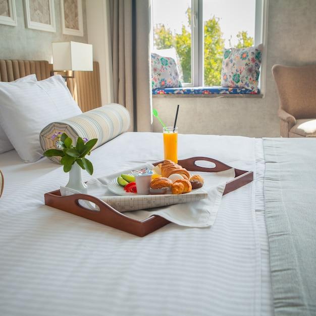Croissant, huevo cocido, jugo de naranja, yogurt desayuno en bandeja en la cama en la habitación del hotel Foto gratis