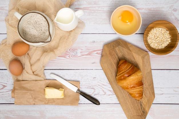 Croissant recién horneado con ingredientes en escritorio de madera Foto gratis