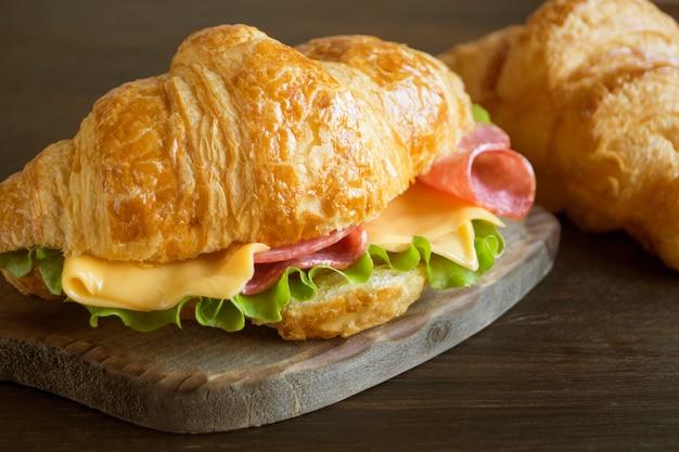 Croissant con salchicha queso y hierbas. sobre fondo oscuro Foto Premium