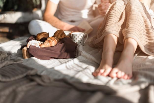Croissant y taza de café cerca de la pareja sentada en la cama Foto gratis
