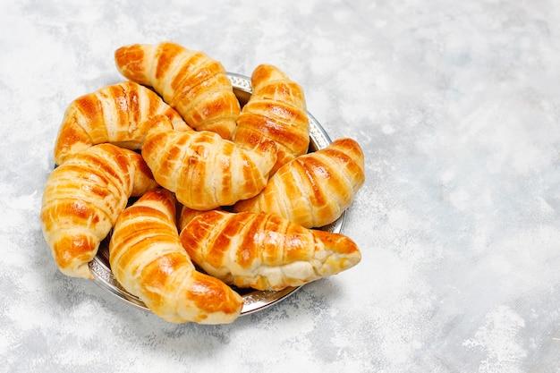 Croissants caseros sabrosos frescos en blanco grisáceo. pastelería francesa Foto gratis