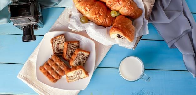 Croissants con crema de chocolate y un vaso de leche sobre la mesa azul. vista superior. Foto gratis