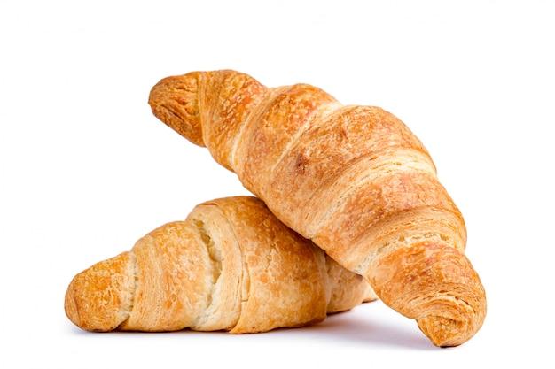 Croissants deliciosos y frescos sobre un fondo blanco. Foto Premium