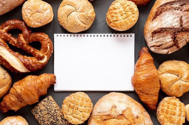 Croissants de pan y una libreta Foto gratis