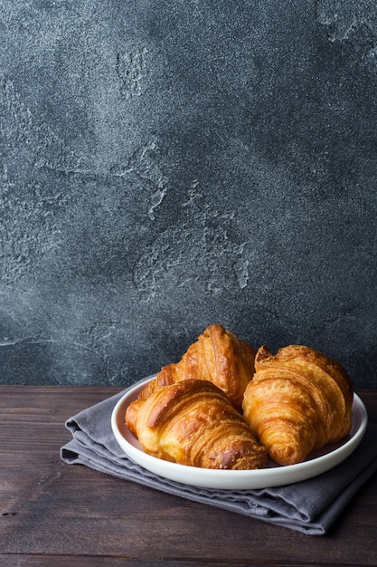 Croissants recién horneados en un plato, fondo oscuro Foto Premium