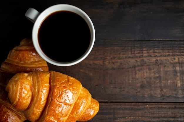 Cruasanes y café en la mesa de madera vieja. Foto gratis