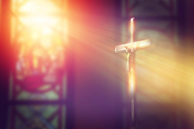 Crucifijo, jesús en la cruz en la iglesia con rayo de luz de vidrieras Foto Premium