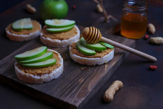 Crujiente sándwich de mantequilla de maní natural con pan de pastel de arroz y rodajas de manzana verde y miel. Foto gratis