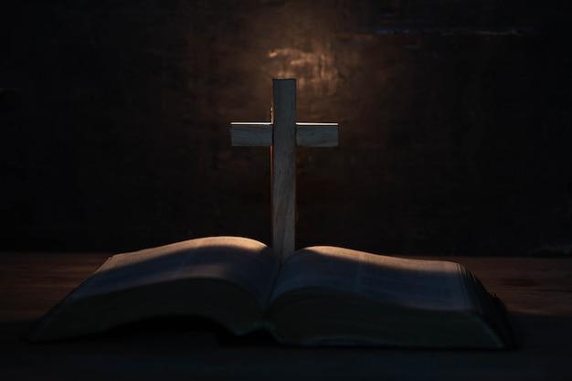 Cruz y santa biblia en mesa de madera Foto gratis