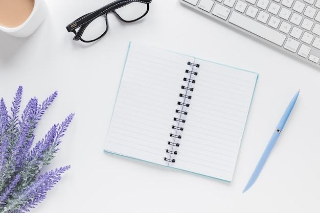 Cuaderno abierto cerca de lavanda, teclado y gafas en el escritorio Foto gratis