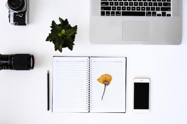 Cuaderno abierto con páginas en blanco de flores, portátil, cámara ...