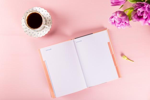 Cuaderno abierto para escribir sueños e ideas con flores cerca. Foto Premium