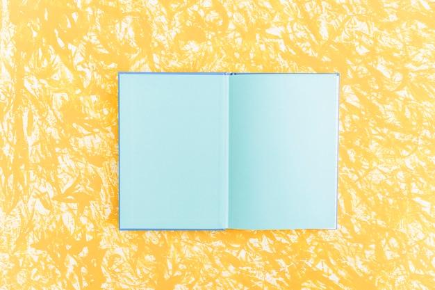 Un cuaderno abierto de páginas azules sobre fondo amarillo con textura Foto gratis