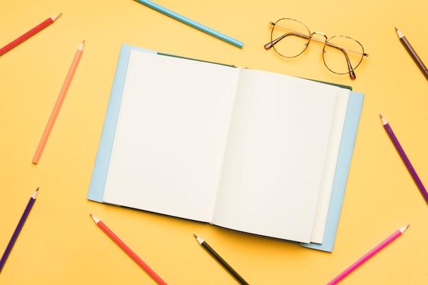 Cuaderno abierto con páginas en blanco rodeadas de lápices Foto gratis