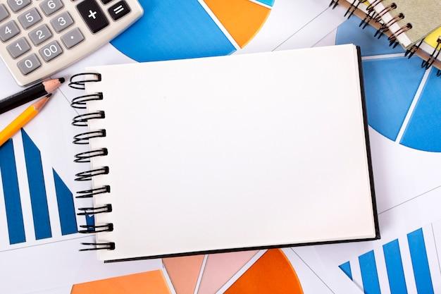 Cuaderno abierto sobre un montón de papeles Foto gratis