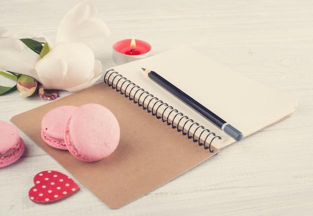 Cuaderno en blanco, macarrones rosas, velas encendidas Foto Premium