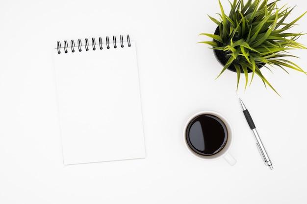 El cuaderno en blanco con la pluma está encima de la tabla blanca del escritorio de oficina con la taza de café. Foto Premium