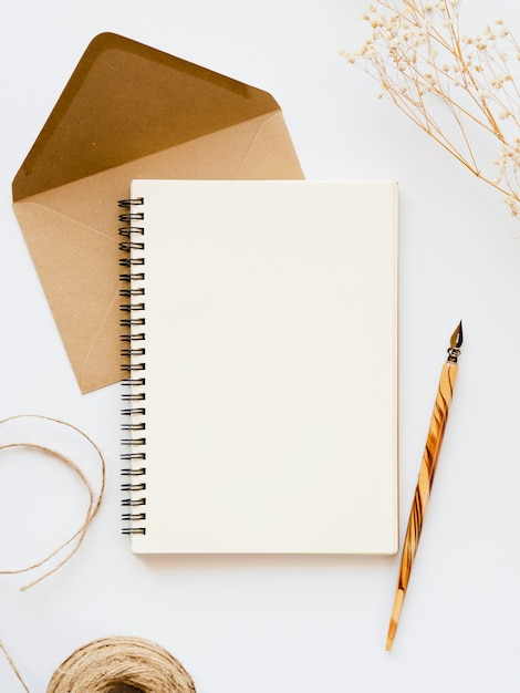 Cuaderno blanco con una punta de madera en un sobre marrón pálido con un hilo marrón y una rama sobre un fondo blanco. Foto gratis