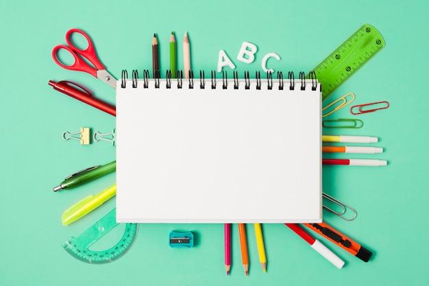 Cuaderno en blanco rodeado de útiles escolares de papelería. Foto gratis