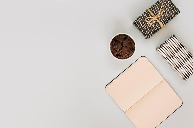 Cuaderno cerca de muffins y regalos Foto gratis