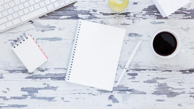 Cuaderno cerca del teclado y la taza de café en la mesa sucia Foto gratis