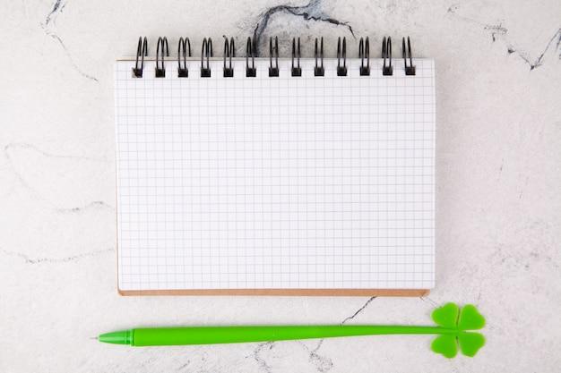 Cuaderno cuadrado sobre un fondo blanco, decoración para el día de san patricio. Foto Premium