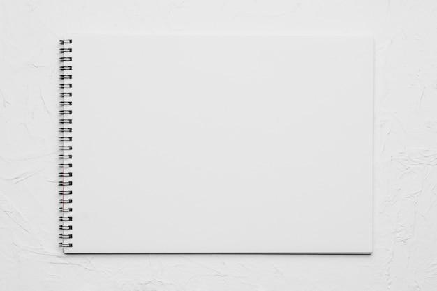 Cuaderno de dibujo vacío blanco sobre superficie rugosa Foto gratis