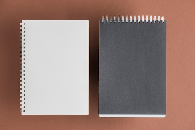 Cuaderno espiral blanco y negro en fondo coloreado Foto gratis