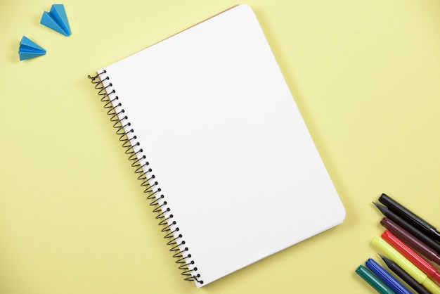 Cuaderno espiral en blanco con rotulador colorido sobre fondo amarillo Foto gratis