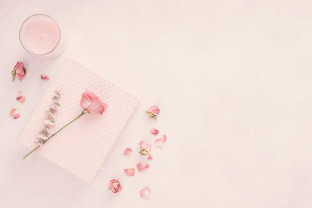 Cuaderno con flor rosa y vela. Foto gratis