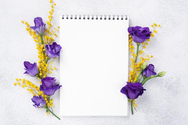 Cuaderno con flores florecientes al lado Foto gratis