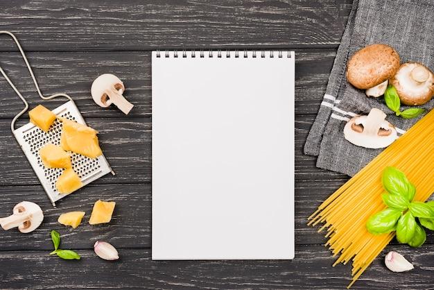 Cuaderno con ingredientes para espagueti con champiñones Foto gratis