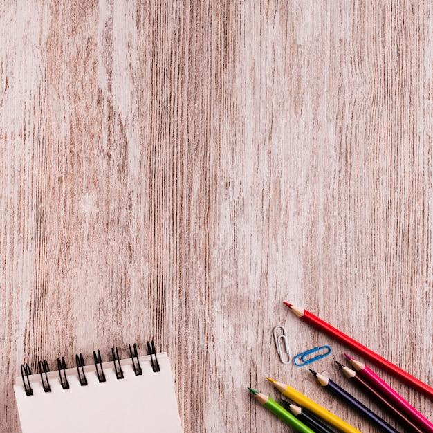 Cuaderno con lápices en superficie de madera Foto gratis
