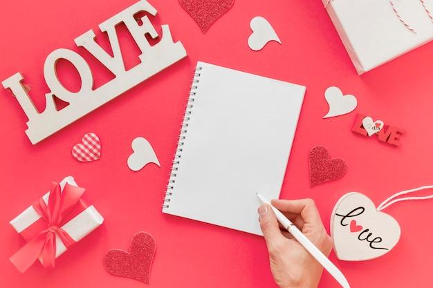 Cuaderno con mano y bolígrafo para san valentín Foto gratis
