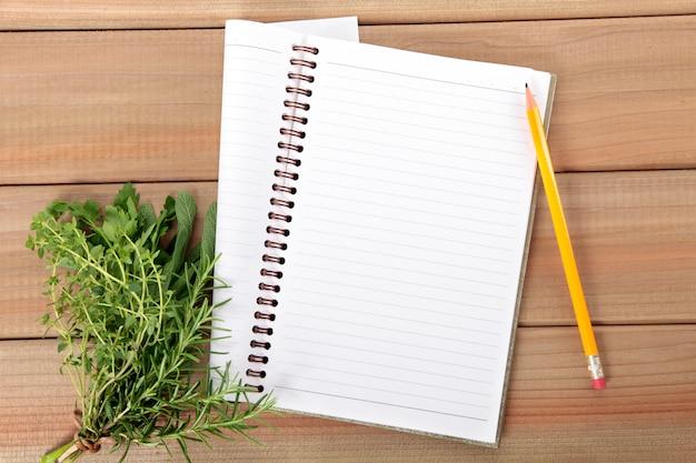 Cuaderno con un manojo de hierbas Foto gratis
