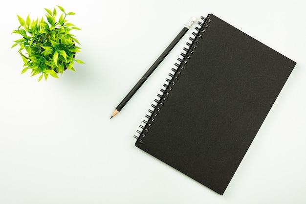 Cuaderno negro y un lápiz - vista superior. Foto Premium