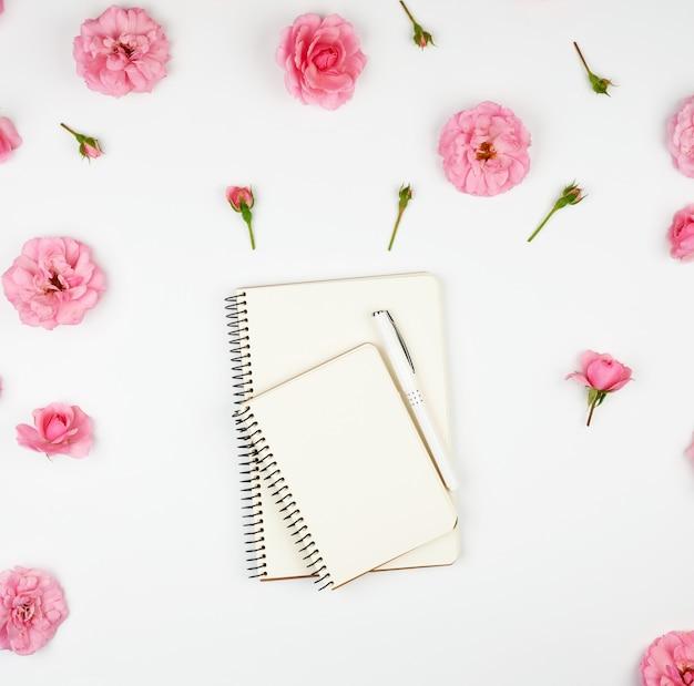 Cuaderno con páginas en blanco en blanco sobre púrpura y rosa con pétalos. Foto Premium