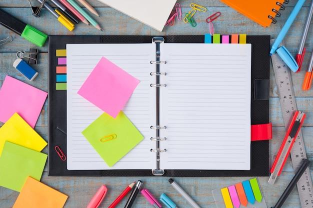 Cuaderno de papel y la escuela u oficina de herramientas en tabla de madera de época Foto gratis